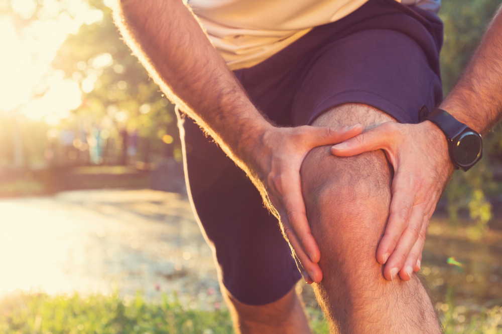 runner holding his knee from knee pain from a sports injury
